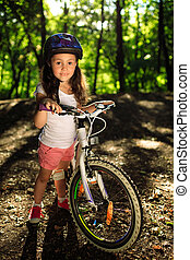 little girl with bicycle in summer park outdoors