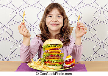 little girl with big hamburger and french fries