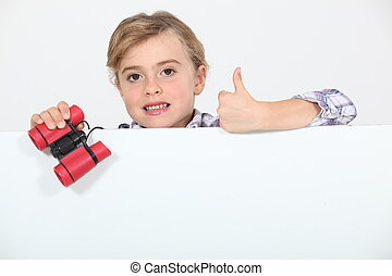 Little girl with binoculars and blank poster