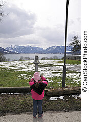 little girl with binoculars at the lake