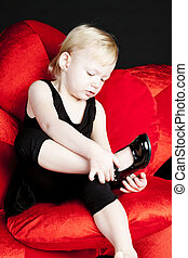 little girl with black shoes sitting on red armchair