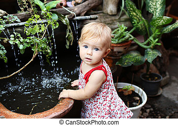 Little girl with blond hair and blue eyes in sundress is standing in garden with pot plants and waterfall.