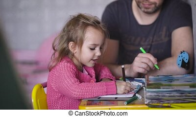 Little girl with blond hair, dressed in a children's blouse, is engaged in drawing together with her dad. The little girl draws a house, and my father grass. They are happy to be together