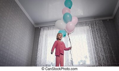 little girl with blond hair, dressed in a pink blouse and pants jumping on the bed, which stands in front of the window and holding colorful balloons in hands