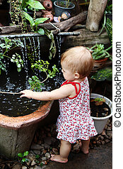 Little girl with blond hair in sundress is standing in garden with pot plants and waterfall and playing with branch of tree.