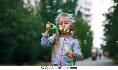 Little girl with blue eyes in a suit, playing with soap bubbles, outdoors, having fun. Slow motion