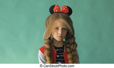 Little girl with braids and a bow in her hair. Posing in the studio