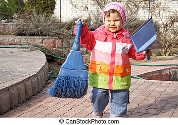 Little Girl with Broom and Trowel Outdoors