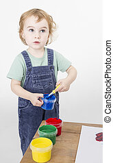 little girl with brush in paint tub