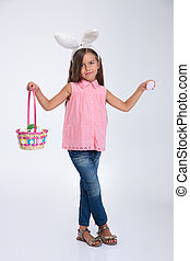 Little girl with bunny ears holding basket of eggs