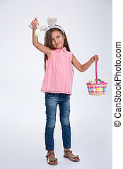 Little girl with bunny ears holding basket of egg