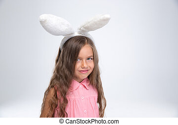 Little girl with bunny ears looking at camera