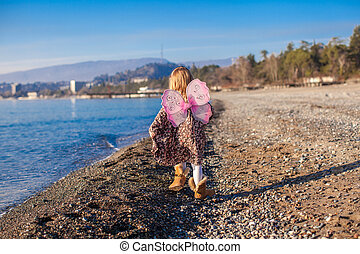 Little girl with butterfly wings running along the beach in a winter sunny day