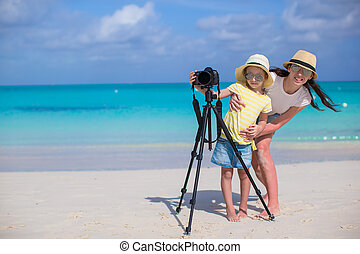 Little girl with camera and young mother on beach