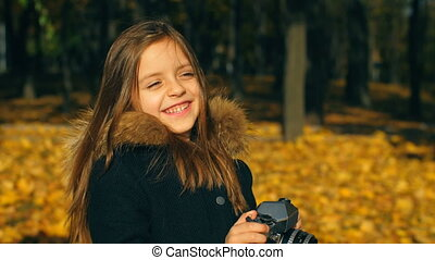 Little girl with camera - Little girl with an old camera at...