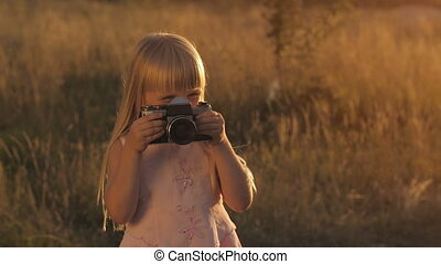 Little girl with camera on nature