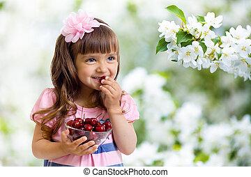 little girl with cherry berries bowl in apple garden