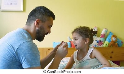 Little girl with chickenpox, eating medicine on spoon -...