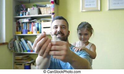 Little girl with chickenpox, father holding antiseptic cream...