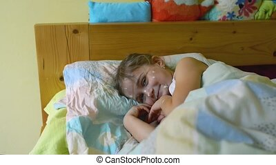 Little girl with chickenpox lying sick in bed.