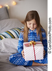 Little girl with Christmas gift in the bed