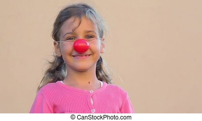 Little girl with clown nose puts hands up and show tongue...