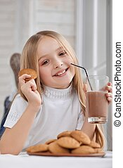 Little girl with cookies and chocolate milk.