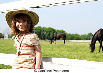 little girl with cowboy hat on farm