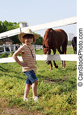 little girl with cowboy hat on ranch