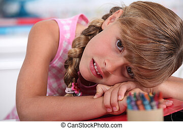 little girl with crayons resting head on desk