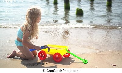 Little girl with curly blond hair playing with sand ant toy cart on sea shore. Child pulling toy wagon with sand and water. Camera motion shot with gimbal.