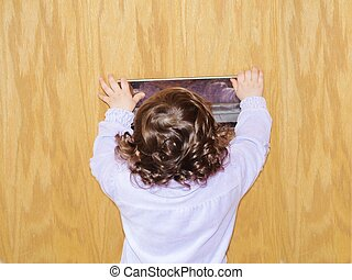 Little girl with curly hair, waiting patiently for the post at door