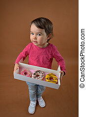 little girl with different donuts
