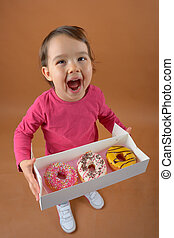 Little girl with different types of donuts