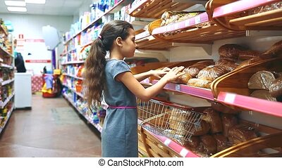 little girl with digital tablet at the grocery store buys bread pastries bakery products online. little girl in the hypermarket concept lifestyle