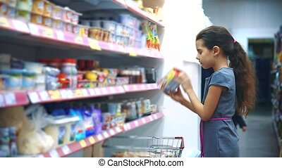 little girl with digital tablet at the grocery store buys buying yogurt milk products online. little girl in the hypermarket concept lifestyle