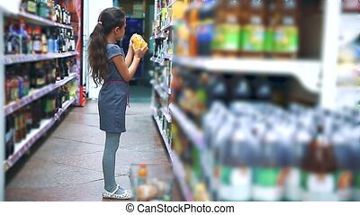 little girl with digital tablet at the grocery store buys...