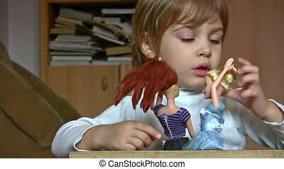 Little girl with dolls, talk , stroke hairs