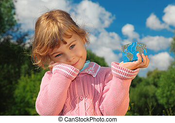 little girl with Earth cube outdoor in summer