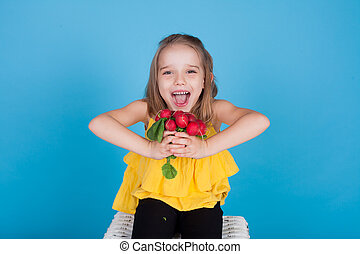 little girl with edible vegetables on a blue background