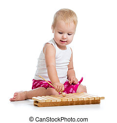 Little girl with excitement playing on xylophone isolated on white.
