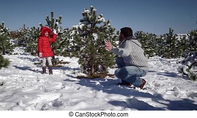 Little girl with father playing with snowballs