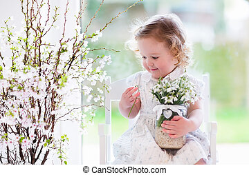 Little girl with first spring flowers at home - Little girl...