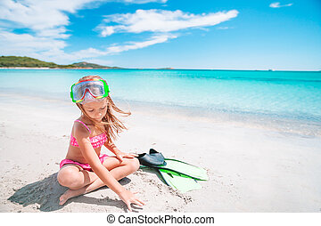 Little girl with flippers and goggles for snorkling on the ...