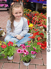 Little girl with flowers around her