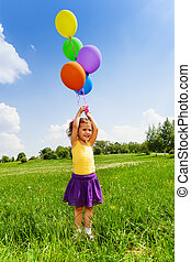 Little girl with flying balloons in the air