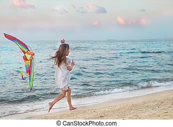Little girl with flying kite on beach at sunset