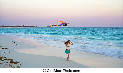 Little girl with flying kite on tropical beach. Kid play on ocean shore. Child with beach toys in slow motion