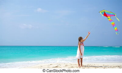 Little girl with flying kite on tropical beach. Kid play on ocean shore. Child with beach toys.