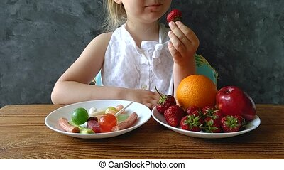Little girl with fresh fruits and sweets on the table at home. Child thinks what to choose healthy or harmful food. HD